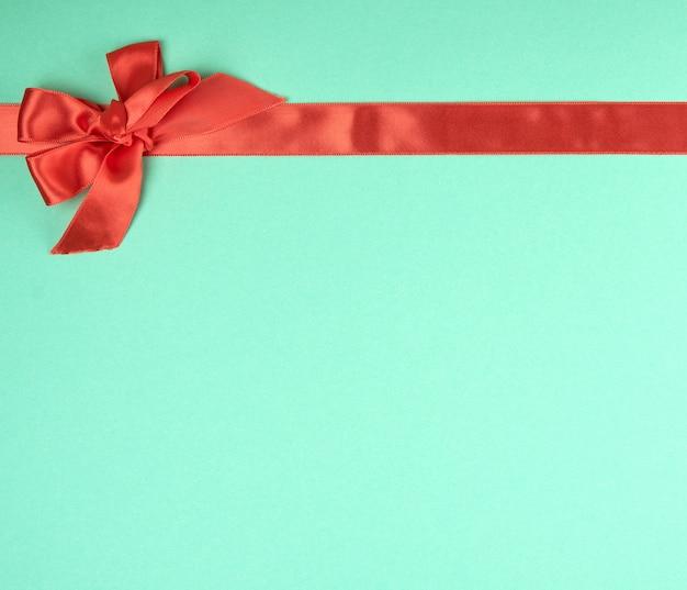 Натянутая красная шелковая лента и бантик, зеленый фон