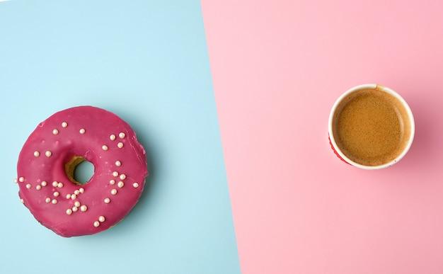 コーヒーと丸い赤い艶をかけられたドーナツと紙コップ