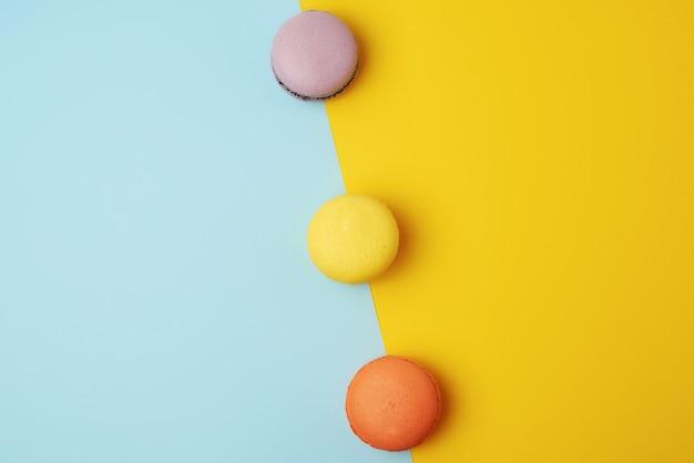 Разноцветные запеченные круглые макаруны на цветном фоне