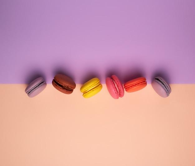 Шесть разноцветных макарон с кремовым фоном