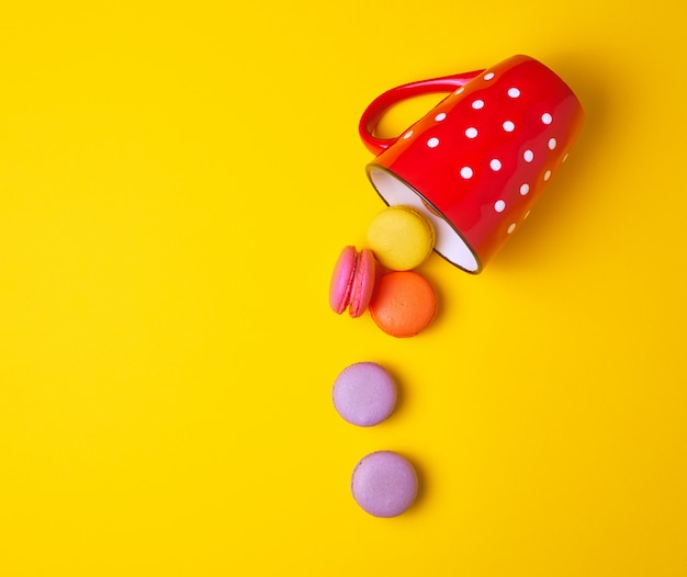 赤いセラミックカップから落ちてくる丸い色とりどりのマカロン