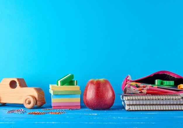 熟した赤いリンゴ、ノートブックのスタックとマルチカラーの木製鉛筆
