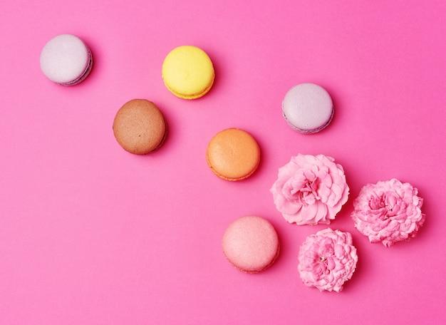 クリームと散乱の花びらの背景を持つピンクのバラのつぼみとマカロン