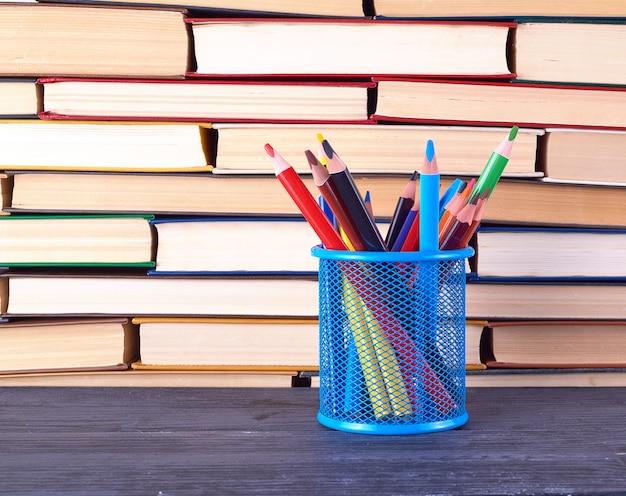 さまざまなハードカバーの本とマルチカラーの木製の鉛筆と青い文房具ガラス