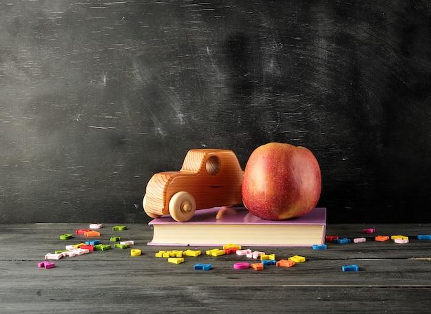 熟した赤いリンゴ、古代のおもちゃの車は本の上に立つ