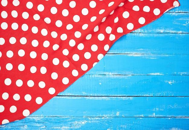 青い木製の背景に白い円で赤い繊維タオル