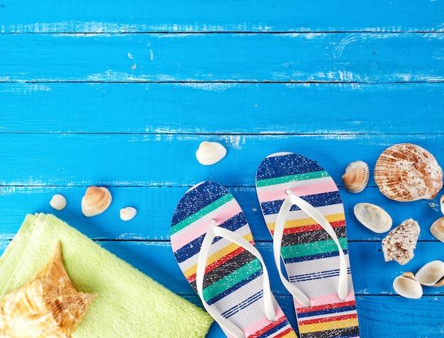 女性のビーチスリッパと緑のタオルのペア