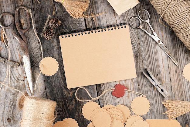 灰色の木製テーブルの上に茶色の空のシートとメモ帳、その横にロープ