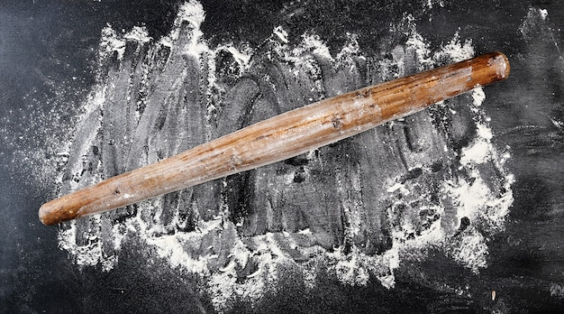 Очень старая деревянная скалка на черном фоне