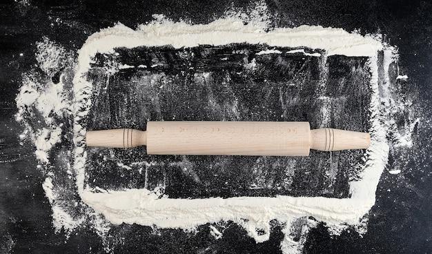 黒の背景、上面に木製麺棒