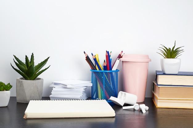 Стопка книг, спиральные тетради, керамическая чашка с кофе и цветные карандаши