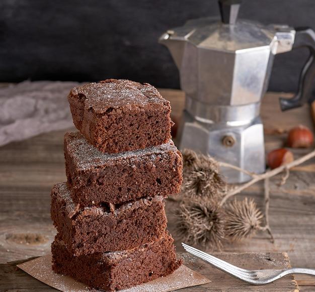 焼きブラウニーチョコレートケーキの正方形のスライスのスタック