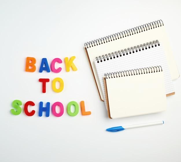 色とりどりのプラスチック文字とノートブックのスタックから学校に戻る碑文