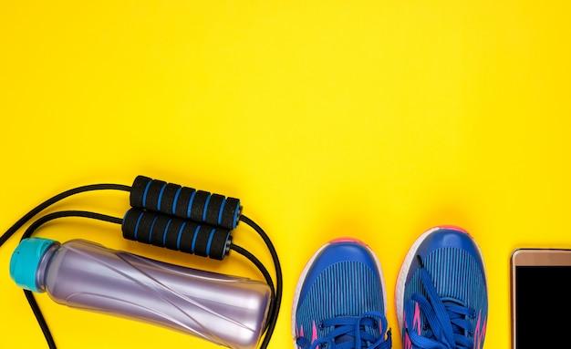 スポーツとフィットネス用の青い女性用スニーカーと縄跳び