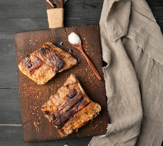 茶色の木製まな板の上のポークリブのグリル、
