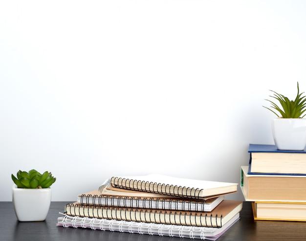 ホワイトページと黒いテーブルの上の植物とセラミックポットとスパイラルノートのスタック