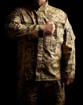 制服を着たウクライナの兵士は暗闇の中で立ち、右手を彼の心に置きます