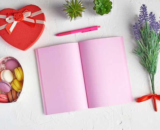 Открытая тетрадь с пустыми розовыми страницами, красным, зеленым карандашом и букетом лаванд на белом, вид сверху