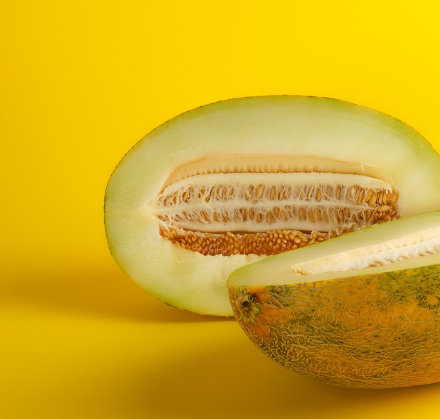Кусочек спелой дыни с семенами на желтом
