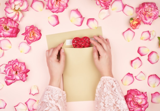女性の手は茶色の紙の封筒に赤いハートを置く