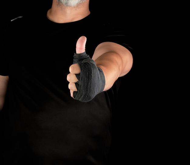 黒い弾性スポーツ包帯に包まれたスポーツマンの手は、同様のシンボルを示します
