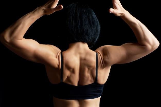 黒い髪の運動少女は彼女に背を向け、筋肉の背中を見せて