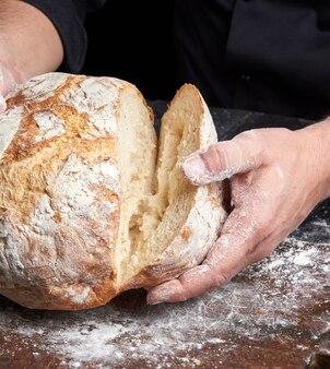 黒チュニックで調理する焼きたてのパンを保持