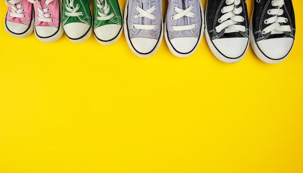 Много изношенных текстильных кроссовок разных размеров на желтом фоне
