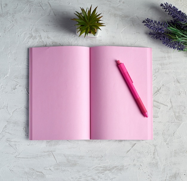 Открытая тетрадь с пустыми розовыми страницами, красным карандашом и букетом лаванд