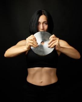 黒い髪とスポーツ図と美しい若い女性はスポーツのための鋼の輪を保持します