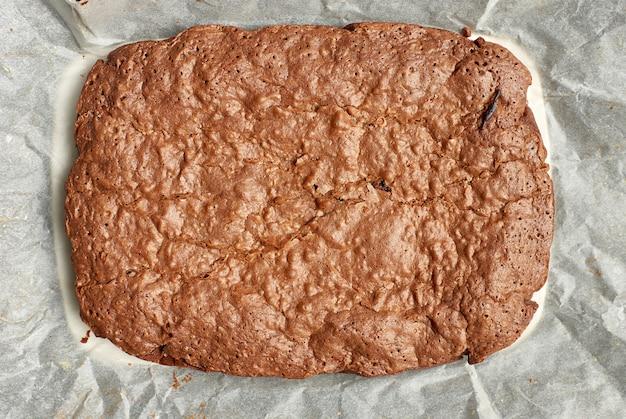 ひびの入った表面を持つ長方形の焼きブラウニーチョコレートケーキ