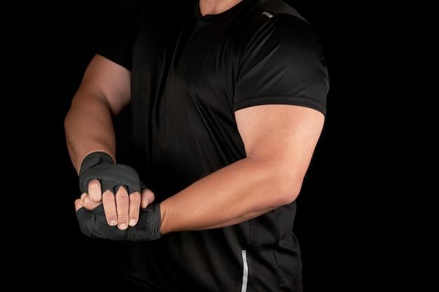 黒い制服を着た大人の運動選手は緊張した筋肉でラックに立っています。