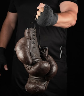 Спортсмен в черной одежде держит очень старые винтажные кожаные черные боксерские перчатки