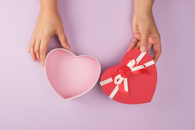Две женские руки держат открытую пустынную красную коробку в форме сердца