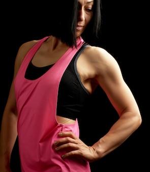 Молодая девушка с черными волосами, одетая в розовую спортивную одежду позирует на темном