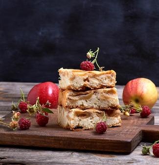 Квадратные кусочки яблочного пирога сложены на коричневой деревянной доске