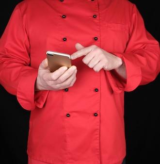 赤い制服を着たシェフが彼の手にスマートフォンを保持します。