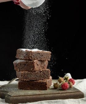 Стопка кусочков шоколадного торта с пирожными, обсыпанными белым сахаром, из железного сита