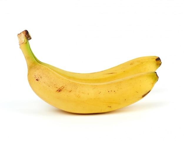Два спелых желтых банана в кожуре на белом