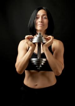 Молодая женщина кавказской внешности держит в руках стальные наборные гантели, спортивная тренировка