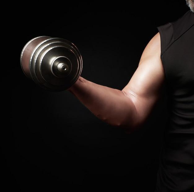 Рука мужчины с большими бицепсами держит стальную наборную гантель, низкий ключ