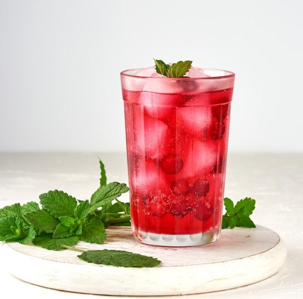 Летний освежающий напиток с ягодами клюквы и кусочками льда в стакане