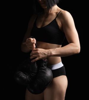 筋肉のついた体を持つ少女は、古い黒のボクシンググローブのペアを保持します