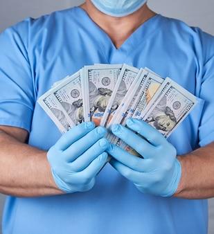 Доктор в синей форме и латексных стерильных перчатках держит много бумажных денег