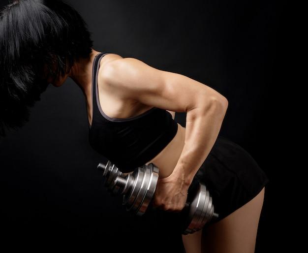 黒髪の大人の女の子はスポーツブラに身を包み、ショートパンツは運動をしています
