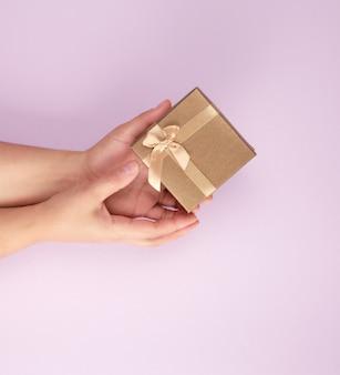 Девушка держит коричневую квадратную коробку на фиолетовом