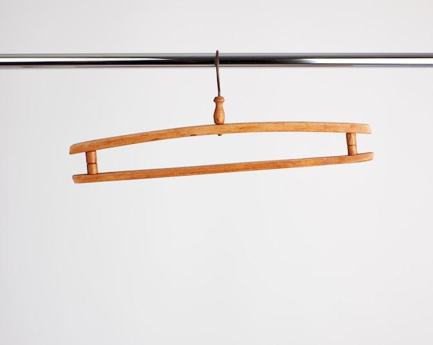 金属パイプに掛かっているヴィンテージの木製ハンガー