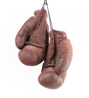 ぶら下がっている非常に古いビンテージブラウンレザーボクシンググローブのペア