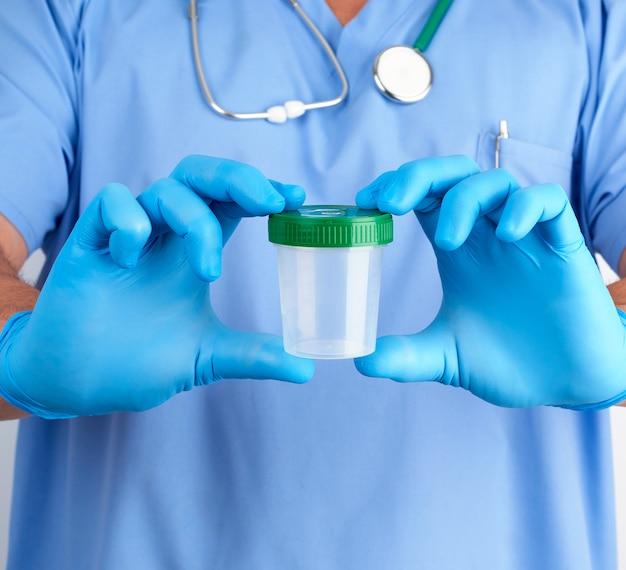Доктор в синей форме и латексных перчатках держит пустой пластиковый контейнер для взятия проб мочи