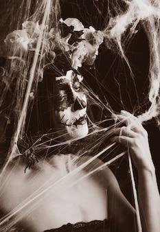 伝統的なメキシコの死のマスクを持つ美しい女性。カラベラカトリーナ。シュガースカルメイク。バラの花輪に身を包んだ女性